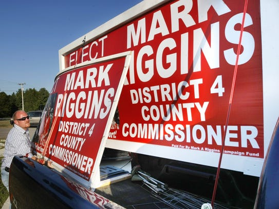 Mark Riggins loads one of his campaign signs from the