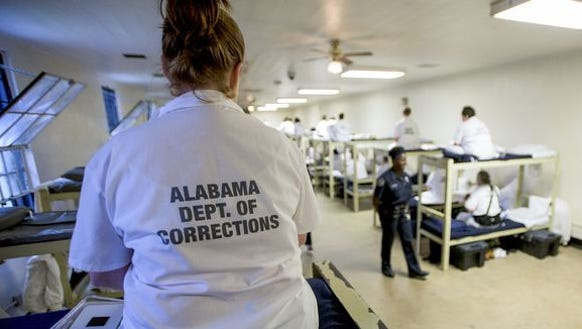 Inmates sit on their bunks as Governor Robert Bentley