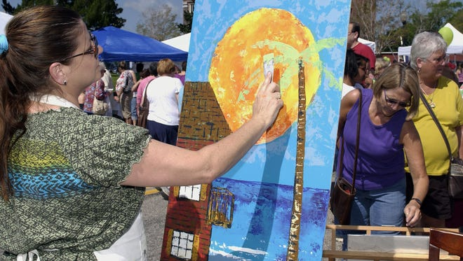 The 29th annual Riverwalk Arts Festival will take place March 3 and 4 in downtown Milton. In this photo from a previous festival, artist Carla D. Milam creates a painting using a putty knife and acrylic paint.