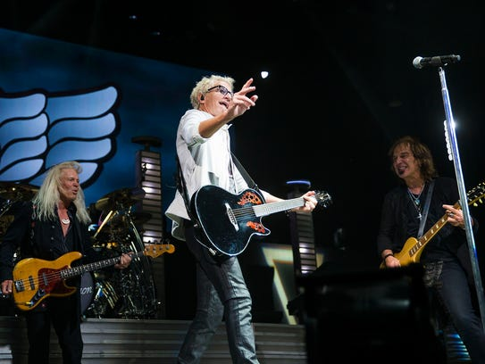 REO Speedwagon front man Kevin Cronin tosses a guitar