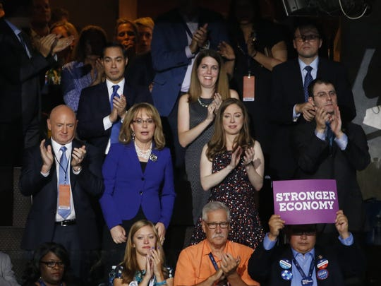 Former U.S. Rep Gabby Giffords (center) stands with her husband and former NASA astronaut Mark Kelly (left) and Chelsea Clinton and her husband, Marc Mezvinsky, during the 2016 Democratic National Convention in Philadelphia on July 27, 2016.