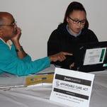 Baps Charities Volunteer Dinesh Patel gets information on health care  plan options.