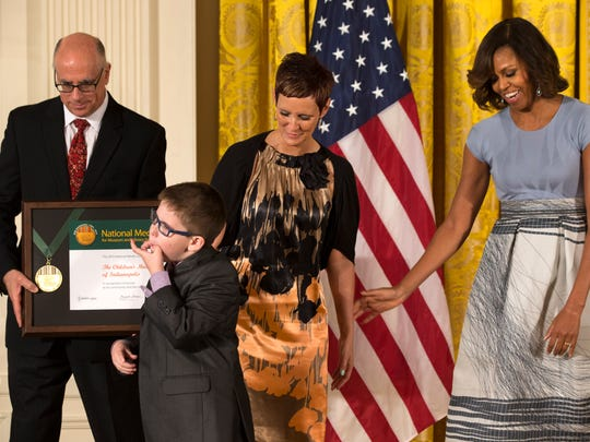 The Children's Museum of Indianapolis President and CEO Jeffrey Patchen, left, holds the museum's 2014 National Medal for Museum and Library Service as Spencer Hahn, 8, who had a stroke in-utero, whistles by his mother Erica Hahn and first lady Michelle Obama during a ceremony in the East Room of the White House, Thursday, May 8, 2014, in Washington. The National Medal is the nation's highest honor given to museums and libraries for service to the community.