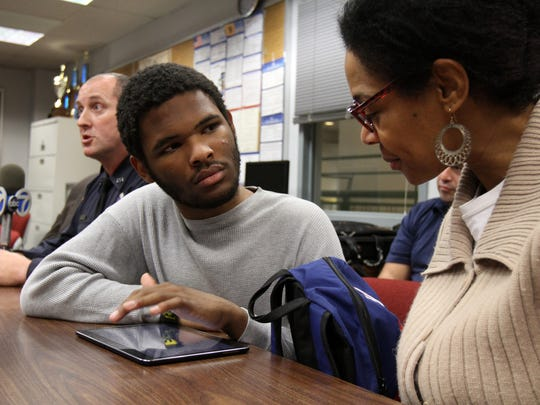 Zion Miller, 16, who is autistic and nonverbal, plays on a tablet, which was a gift from Franklin Township Police Officer Richard Hartnett (left) and donated by Jim O'Neil of Electronics Enterprise in Somerset (not shown), with his mother, Kimora Miller, of Franklin, during a press conference about the gift at Franklin Township Police Department in Somerset on Thursday, Dec. 3, 2015.