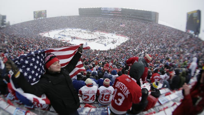 Nate Hamel, 21, of Big Rapids poses for a photo as he wraps himself in the American flag before the 2014 Bridgestone NHL Winter Classic between the Detroit Red Wings and Toronto Maple Leafs at Michigan Stadium in Ann Arbor on Jan. 1, 2014.