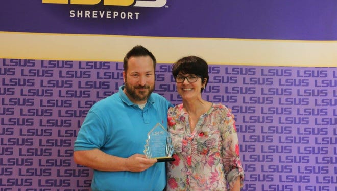 Rhonda Failey is presented with the award for Professor of the year by LSUS SGA president Dennis Henderson.