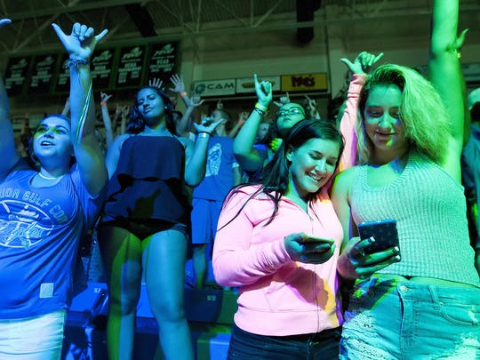 FGCU students Kayla Frame, 21, second from left, and Riena Casa, 19, check a university app on their smartphones Wednesday at the Eagle Revolution pep rally at FGCU in Fort Myers.