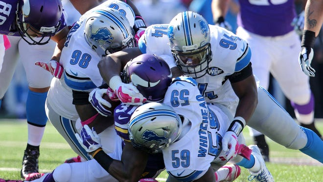 Minnesota Vikings running back Jerick McKinnon (31) is tackled by Detroit Lions defensive tackle Nick Fairley (98), linebacker Tahir Whitehead (59) and defensive end Ezekiel Ansah (94) during the first quarter at TCF Bank Stadium.
