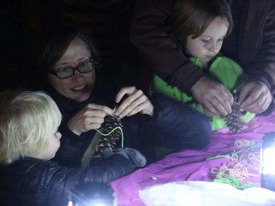 Michelle Rittenhouse, center, helps her sons Lucas and Isaac make pine cone bird feeders during the Winter Solstice Celebration on Sunday at the Edwin Warner Park Nature Center.