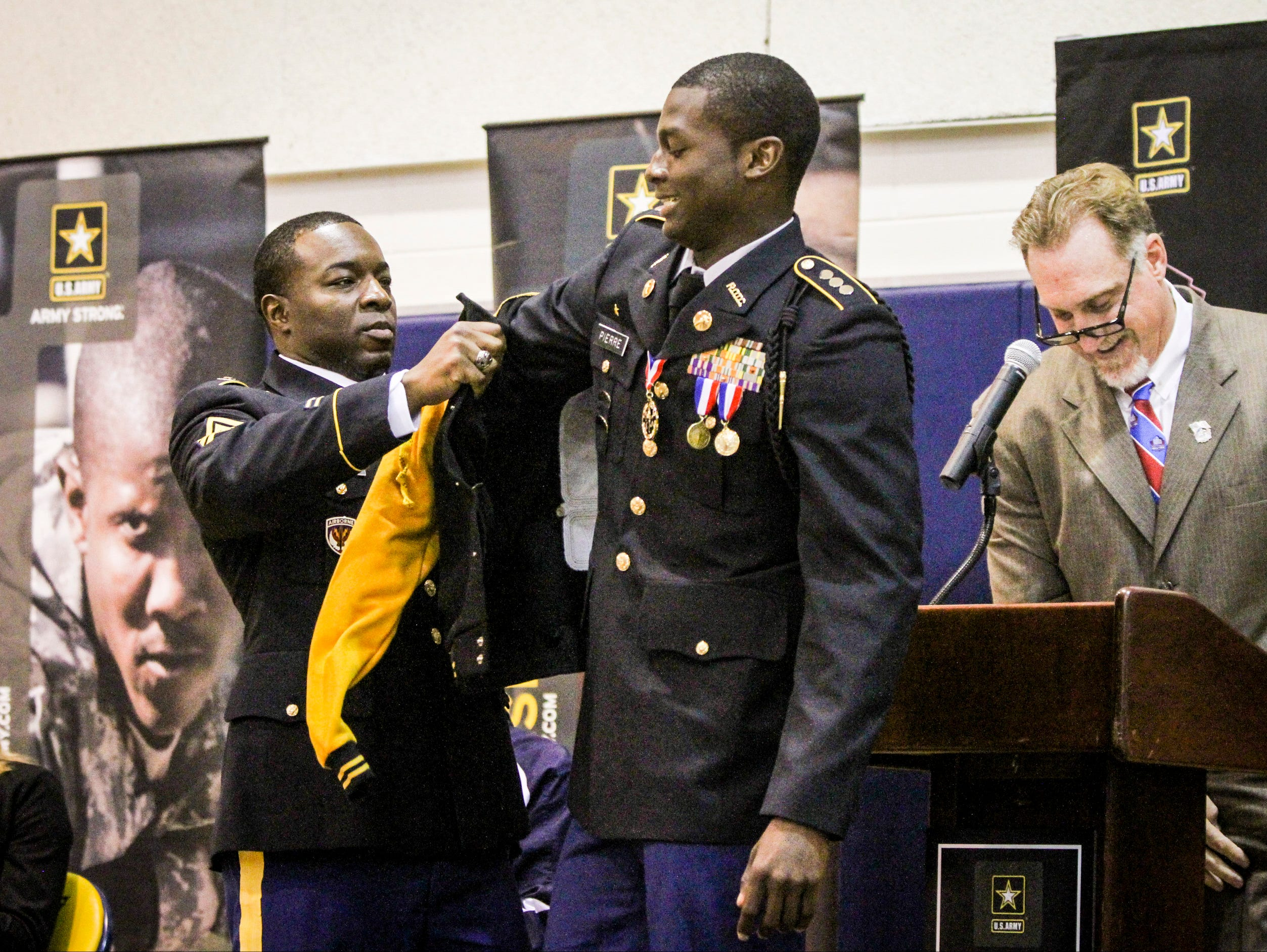 Pierre puts on a Gold jacket from the US Army. Lehigh Senior High senior Wadley Pierre was nominated as a finalist for the US Army and Pro Football Hall of Fame as a student-athlete finalist for an award of excellence. Hall of Fame NFL player Kevin Greene was there to present the recognition.