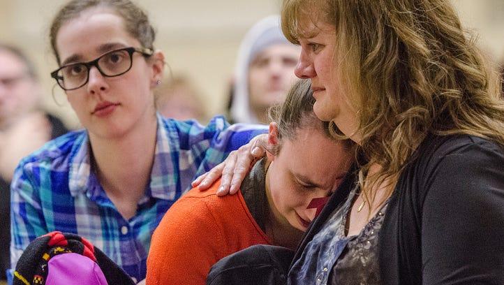 Ann Stislicki comforts daughter Jillian Stislicki at a vigil in Redford. Daughter Holley Stislicki is at left.