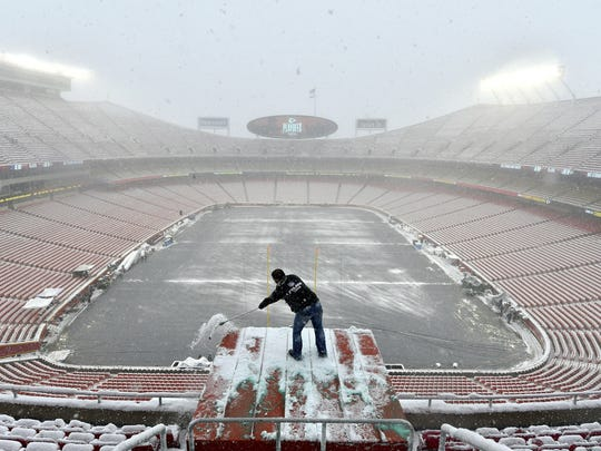 Kyle Haraugh, of NFL Films, clears snow from a camera location at Arrowhead Stadium before an NFL divisional football playoff game between the Kansas City Chiefs and the Indianapolis Colts, in Kansas City, Mo., Saturday, Jan. 12, 2019.