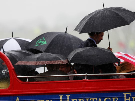 Race goers shelter underneath umbrellas from the rain as they arrive on a open top double-decked bus for the Epsom Derby at Epsom racecourse, England, Saturday, June 7, 2014. (AP Photo/Sang Tan)