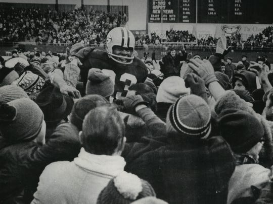 Running back Travis Williams is cheered on by fans after leading the Green Bay Packers' 28-7 victory over the Los Angeles Rams at County Stadium in the playoffs in 1967.