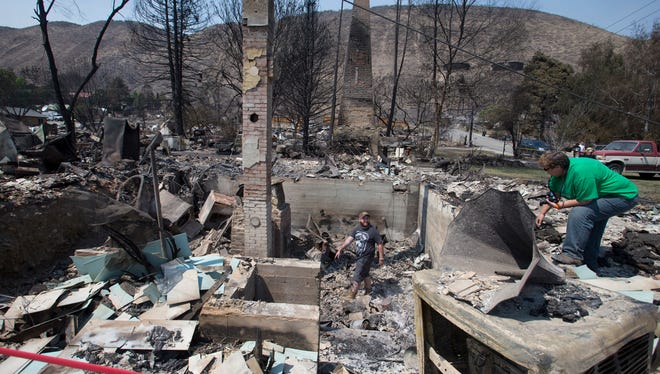 On Monday July 21, 2014, Jake Hixon, center and Kathy Harding look for family heirlooms they may have been spared at a relatives house after the wildfire that swept through Pateros, Wash., last Thursday.
