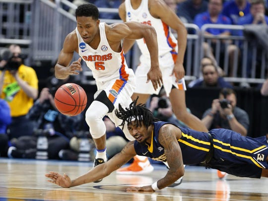 East Tennessee State guard T.J. Cromer, foreground, is unable to take a loose ball from Florida guard KeVaughn Allen (5) during the second half of the first round of the NCAA college basketball tournament, Thursday, March 16, 2017 in Orlando, Fla. (AP Photo/Wilfredo Lee)
