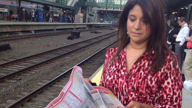 Commuter Damaris Claudio looks over the new New Haven Line timetable at the New Rochelle station May 12, 2014.