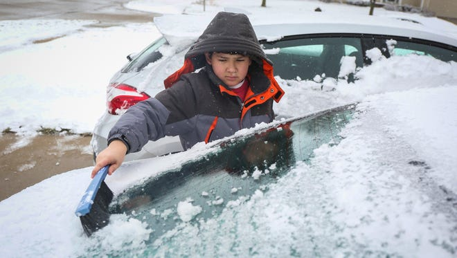 Gavin Firch, 11, cleans snow off his grandma's car in West Des Moines after a winter storm dumped snow across parts of central Iowa on Sunday, April 15, 2018.