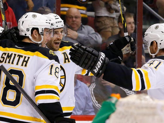 Boston Bruins' Patrice Bergeron, second from left, celebrates his goal against the Coyotes with teammates Reilly Smith (18) and Andrej Meszaros (41), of the Czech Republic, during the first period of an NHL hockey game on Saturday, March 22, 2014, in Glendale.