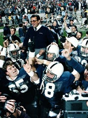 FILE - In this Jan. 2, 1987, file photo, Penn State coach Joe Paterno is carried off after they defeated Miami 14-10 in the Fiesta Bowl NCAA college football game in Tempe, Ariz., to win the national championship. A proposed settlement, announced Friday, Jan. 16, 2015, by the NCAA, will give Penn State back 112 football team wins that were vacated two years ago in the Jerry Sandusky child molestation scandal.  If approved, the new agreement also would restore former coach Paterno's status as the winningest coach in major college football history with 409 victories.  (AP Photo/Jim Gerberich, File)