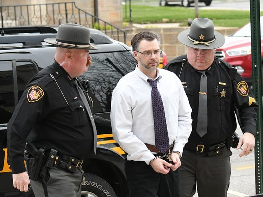 Two Ashland County Sheriff deputies escort suspected serial killer Shawn M. Grate to Common Pleas Court in Ashland on Monday morning for the first day of his trial. Grate is charged with 23 counts, including aggravated murder.