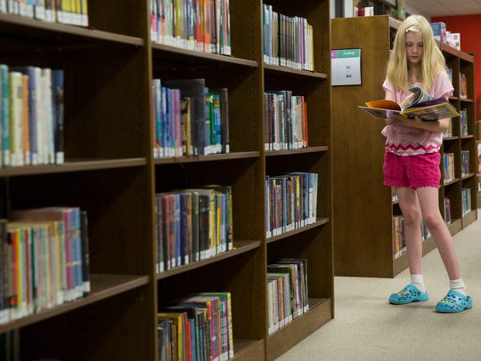 Kacey Hudson, 10, picks out books at the Henderson