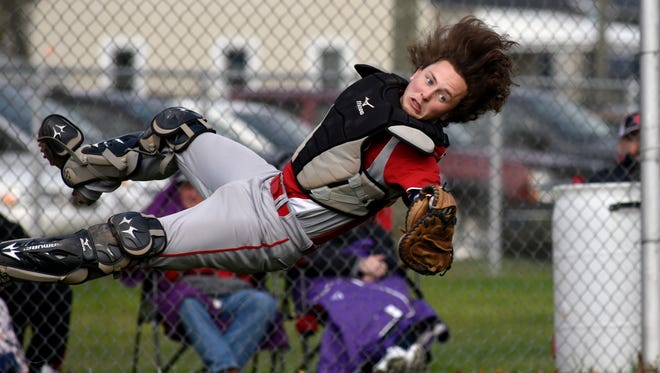 Saints' catcher Sam Winston makes a diving catch for a foul ball Monday, April 17, during boys baseball action at Port Huron High School.