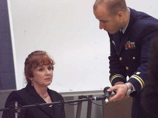 """Elizabeth Helmbrecht, left, driver of the tour boat """"Miss Majestic,"""" prepares to testify before a U.S. Coast Guard hearing Tuesday, May 11, 1999, in Hot Springs, Ark., as Lt. j.g. Brian Knapp adjusts her microphone. The tour boat sank in Lake Hamilton near Hot Springs on May 1, leaving 13 dead. (AP Photo/Danny Johnston)"""