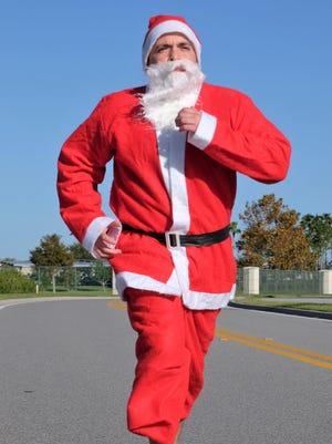 The sprinting Santa, aka Mike Acosta, is race director for the new Run Run Santa 1-Miler.