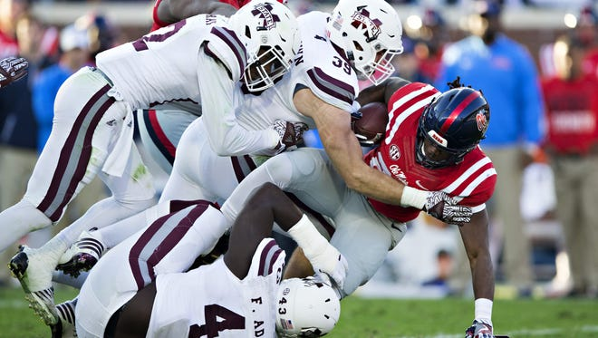Richie Brown #39 of the Mississippi State Bulldogs tackles Eugene Brazley #23 of the Mississippi Rebels at Vaught-Hemingway Stadium on November 26, 2016 in Oxford, Mississippi.