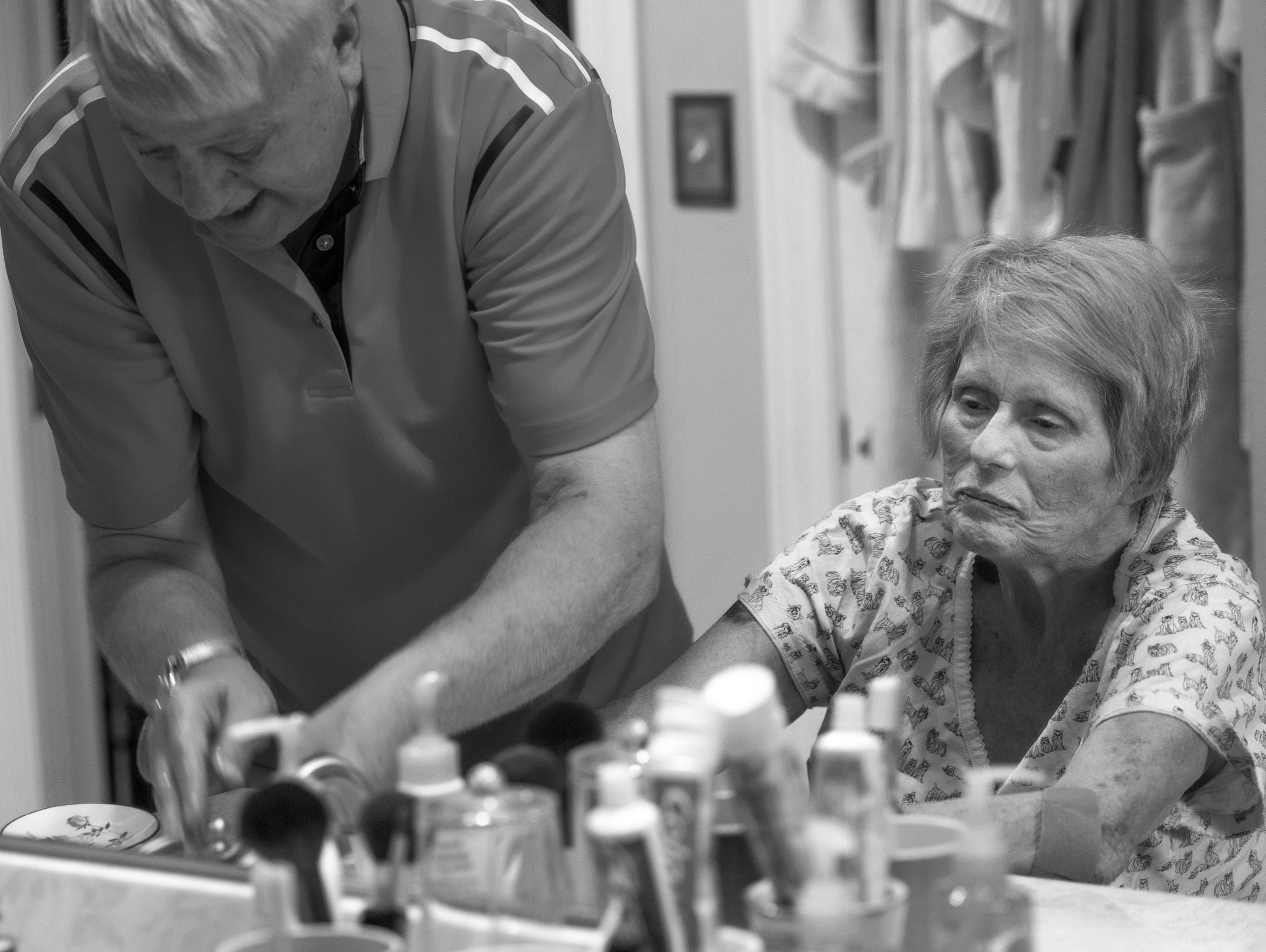 Fred helps Patty wash her hands in their master bathroom