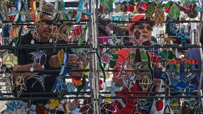 Ed and Camilla Conell from Cherry Hill take a close look at the stained glass stand during the 2015 Collingswood May Fair.