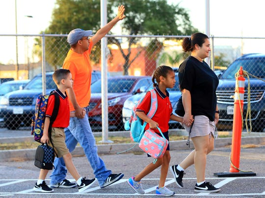 Parents walk with their children on their first day of classes on Wednesday, Aug. 23, 2017, at the School of Science and Technology in Corpus Christi.