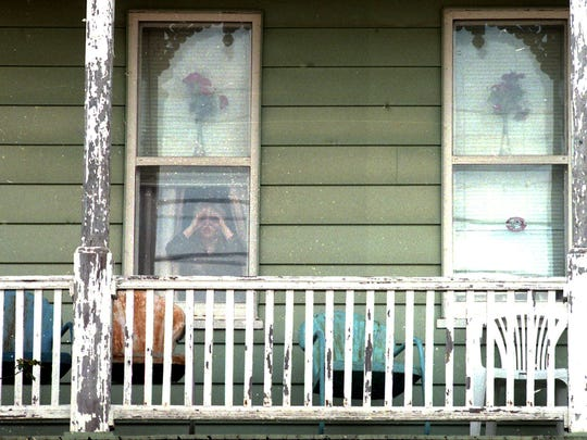 Sauder Cummings' older brother peers out of his grandmother's kitchen window on Nov. 21, 1996 in Yoe, a small borough southeast of York, near Dallastown. Earlier that day, the boys' father, Jack Cummings Jr., shot and killed their mother Shelle and then himself.
