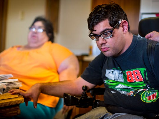 "Louis Facenda, Jr. with his mother Joann Facenda, left, Wednesday, August 30, 2017, at their West Des Moines home.  Louis Facenda, Jr.  spent as much as half his day in a dirty diaper this summer, an issue his mother and caregiver insists is a direct result of Iowa Medicaid management's profit motive. ""Who do you blame? Who fixes this stuff,"" an exasperated Joann Facenda of West Des Moines asked."