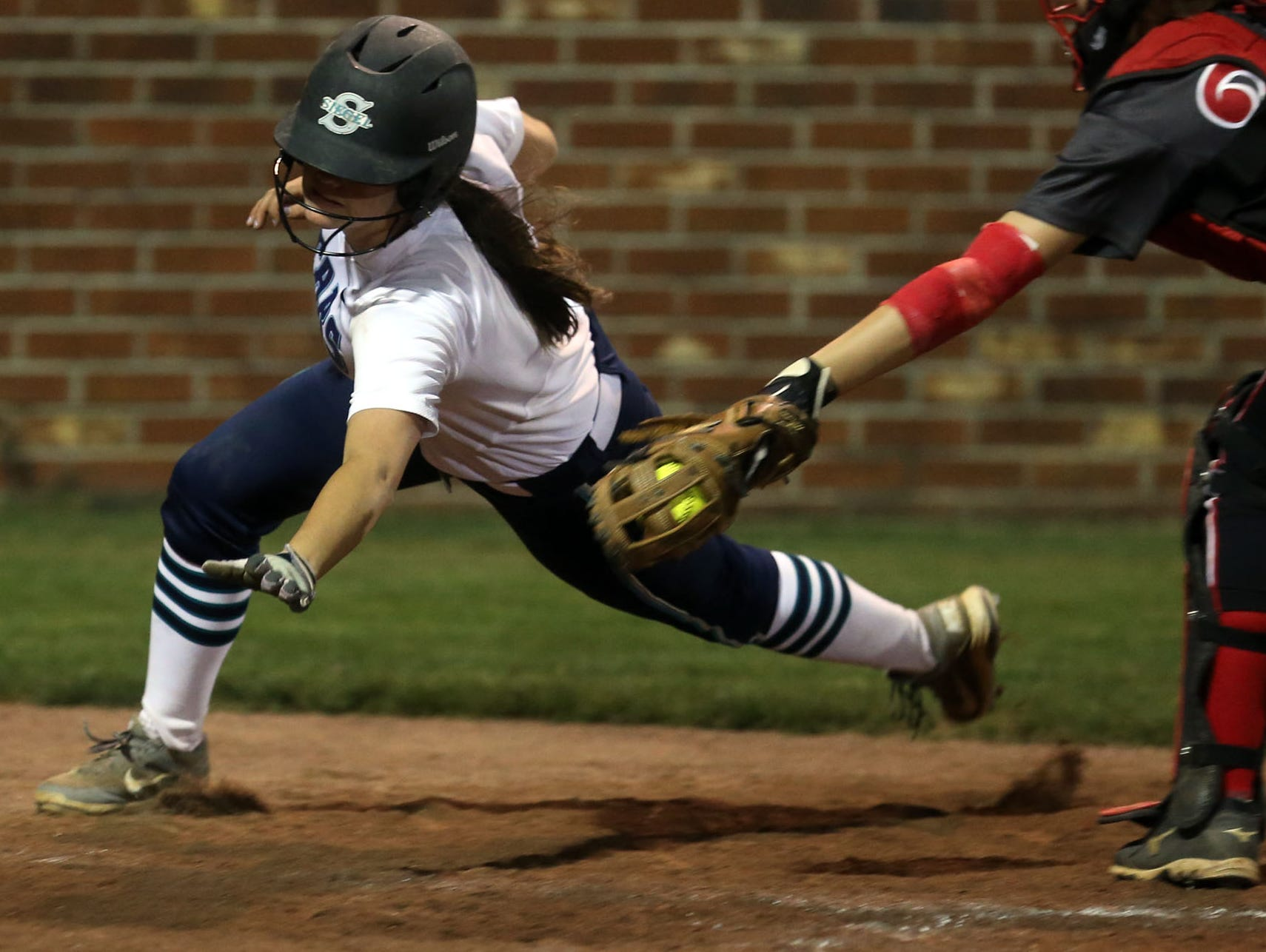 Siegel's Rebekah Juergens tries to score around Coffee County catcher Tori Bell in the 11th inning Wednesday at Coffee County. Juergens was called out on the play.