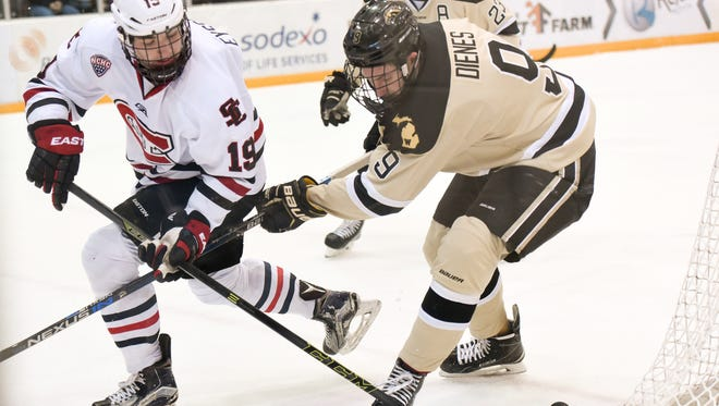 St. Cloud State's Mikey Eyssimont (left) flips the puck from behind the goal past Western Michigan's Chris Dienes last season at the Herb Brooks National Hockey Center. Eyssimont has 22 goals and 47 points in 54 games for the Huskies.