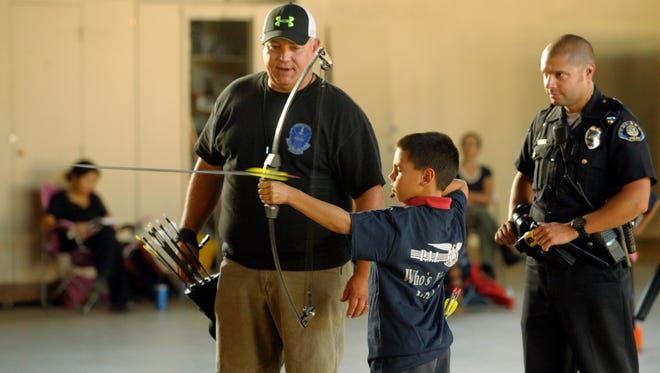 Tulare Police Capt. Wes Hensley, left, and Officer Michael Melikian assist David Porter, 9, while he shoots among 30 kids ranging in ages from 8-18 Thursday night during the Tulare's Police Activity League's archery program inside the California National Guard Armory, 649 E. Cross Ave., Tulare.