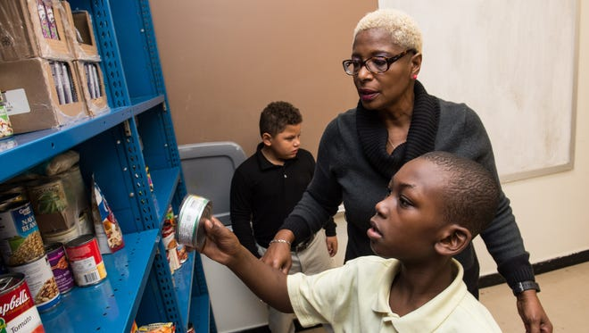 Patricia Fontaine helps students Ta'Shy Parker, right, and Jayden Joseph stock shelves at the Marion Sarah Peyton Adult and Alternative Learning Center on Monday, Nov. 27, 2017.