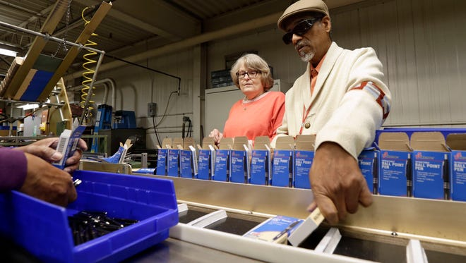 In this Monday, April 16, 2018, photo, employees Lynn Larsen, left, and Clifford Alexander Sr. box SKILCRAFT pens for the U.S. Government at the Industries of the Blind in Greensboro, N.C. Government pens have been manufactured for 50 years by National Industries for the Blind. (AP Photo/Gerry Broome)