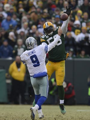 Green Bay Packers linebacker Julius Peppers tries to swat a pass by Dallas Cowboys quarterback Tony Romo during the second quarter of Sunday's NFC divisional playoff game at Lambeau Field.