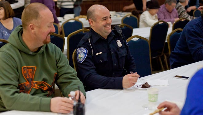Port Huron police Officer William Sharp laughs while sitting with Lt. Joseph Platzer, left, and others during a law enforcement appreciation dinner Wednesday at the Charles A. Hammond American Legion Post 8 in Port Huron.