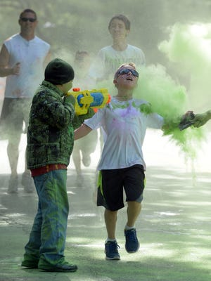 Volunteers cover runners with color during the 2014 City Fit 4-H Color Run as part of Richmond's City Fit at Glen Miller Park.