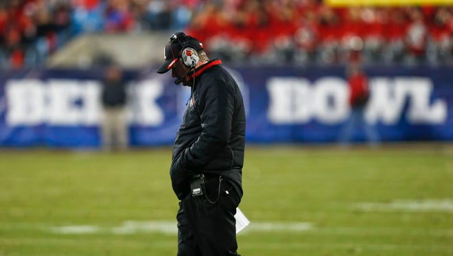 Louisville head coach Bobby Petrino walked slowly towards midfield late in the fourth quarter during a time out at the 2014 Belk Bowl in Charlotte, North Carolina Tuesday evening. Georgia easily beat Louisville 38-14.  Dec. 30, 2014 By Matt Stone/The Courier-Journal