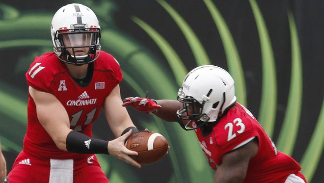 Gunner Kiel (11) hands off to Hosey Williams (23) during football practice.