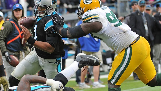 Green Bay Packers nose tackle Letroy Guion (98) shoves Carolina Panthers quarterback Cam Newton (1) out of bounds on a run at Bank of America Stadium in Charlotte, N.C., November 8, 2015.