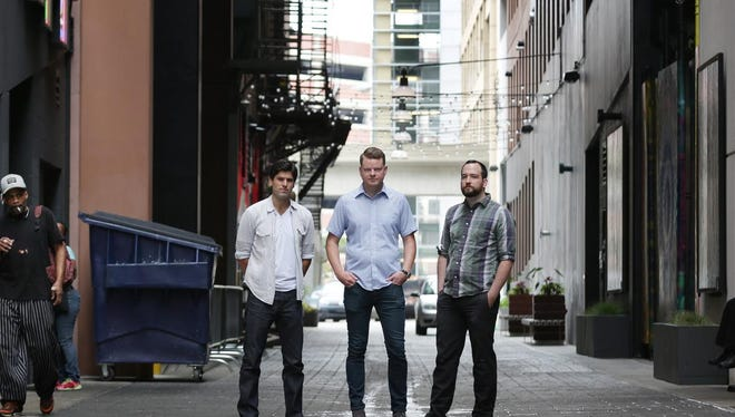 Real estate developer Anthony Curis, from left, bartender and spirits consultant Joe Robinson, and chef Brendon Edwards stand in the art-filled Belt alley where their future Skip will be..
