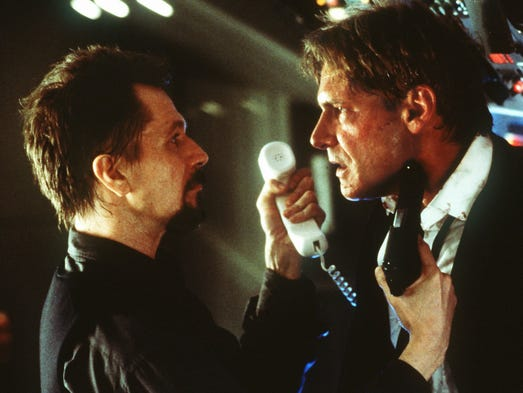 "Gary Oldman portraying a Russian ultranationalist terrorist hijacker, holds a gun to Harrison Ford, who plays the president of the U.S., in a scene from ""Air Force One."""
