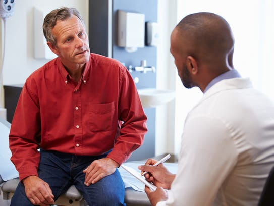 A man discusses feelings of depression with his doctor.