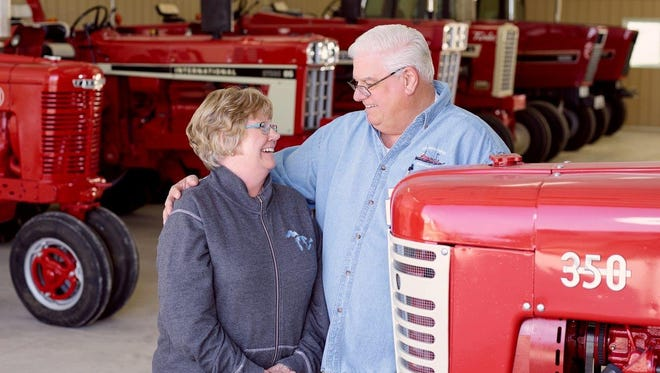 Jelaine and Pete Horton pose among Pete's collection of International Harvester tractors in Sturgeon Bay.